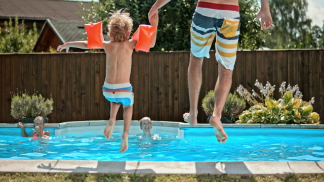 slo mo ds father and son jumping into the pool - swimming pool stock videos & royalty-free footage