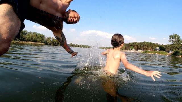 vater und sohn springen ins wasser - sprung wassersport stock-videos und b-roll-filmmaterial