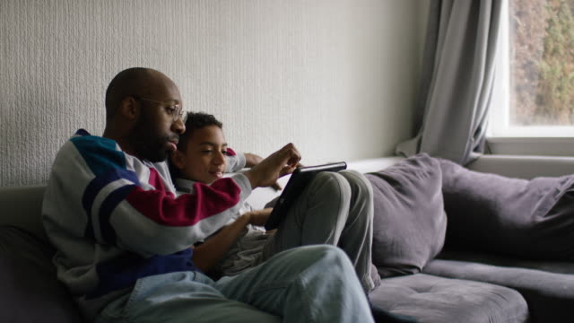 a father and son look at a digital tablet together - adolescence stock videos & royalty-free footage