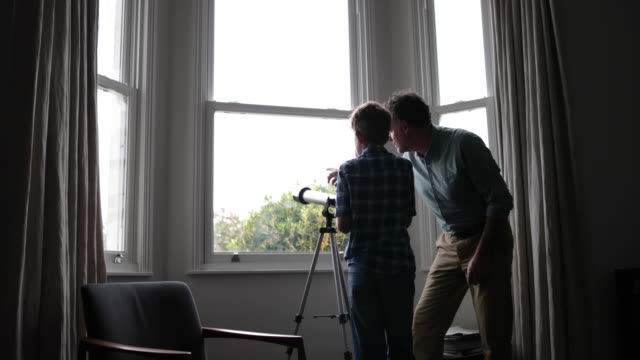 vídeos de stock, filmes e b-roll de father and son looking at view with a telescope - janela saliente