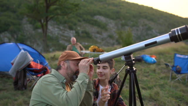 father and son looking through telescope on mountain - see through stock videos & royalty-free footage