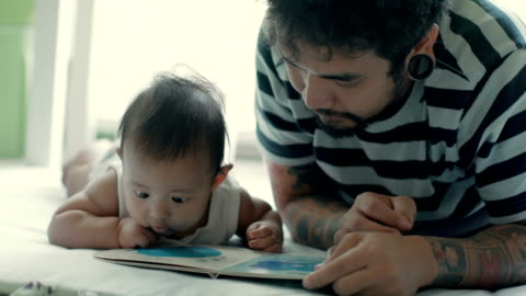 father and son lying to read a book on the mat (0-11 months), thailand - 0 11 months stock videos & royalty-free footage