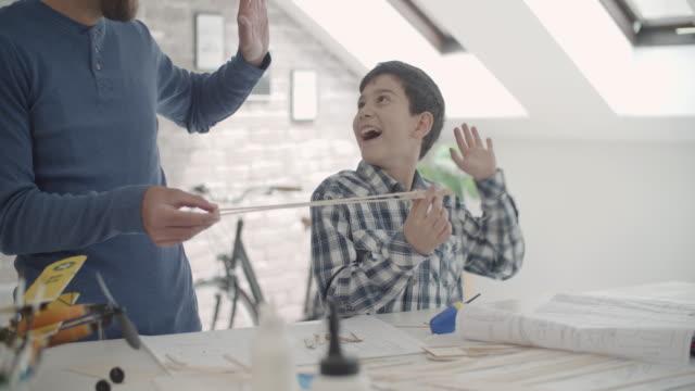 vídeos y material grabado en eventos de stock de padre e hijo haciendo un avión de juguete - avión de papel