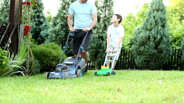 HD: Father and son mowing grass in a backyard.