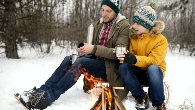 vidéos et rushes de père et fils près du feu de camp dans la nature - son