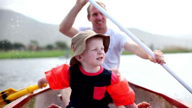 father and son on a paddle boat in the water - paddle boat stock videos & royalty-free footage