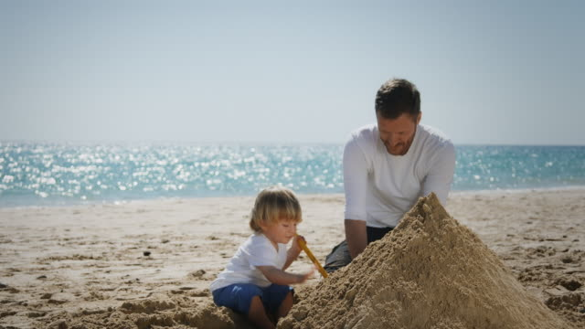father and son on beach - sand stock videos & royalty-free footage