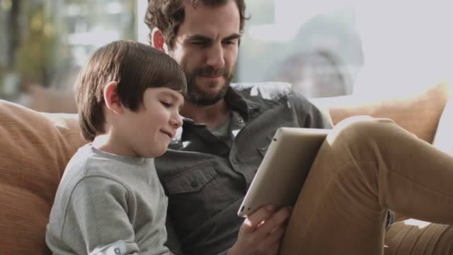 father and son on the couch using digital tablet - using digital tablet stock videos & royalty-free footage