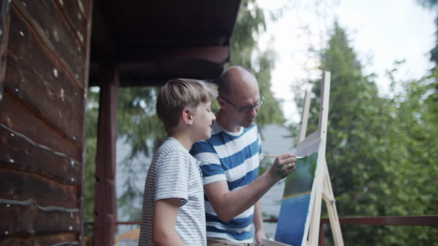 father and son painting on canvas - modern manhood stock videos & royalty-free footage