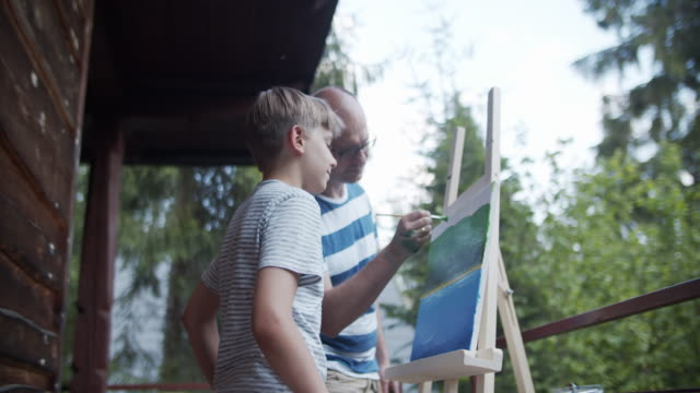 father and son painting on canvas - candid stock videos & royalty-free footage