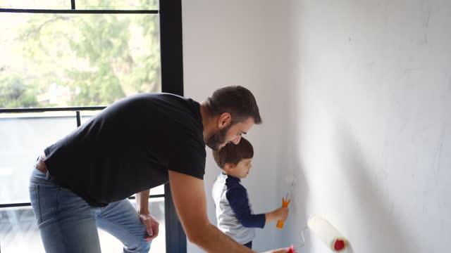 padre e figlio dipingendo le pareti - bricolage video stock e b–roll