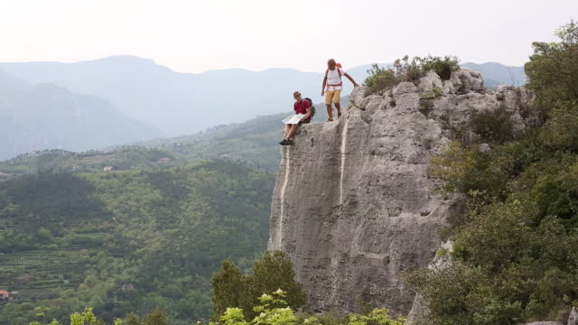 father and son pause on hike to rock crest above valley, mountains - son stock videos & royalty-free footage