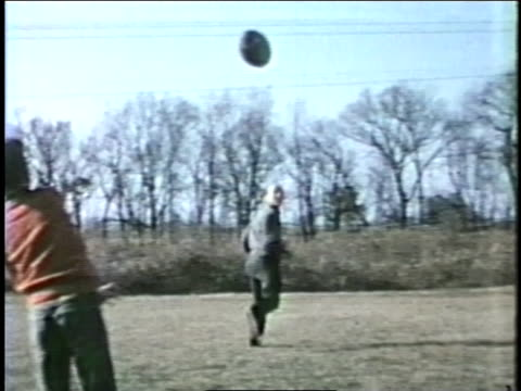 a father and son play catch with a football in a field. - american football ball stock videos & royalty-free footage
