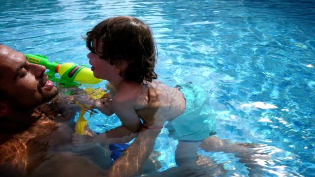 父と息子のプールで演奏 - 水鉄砲点の映像素材/bロール