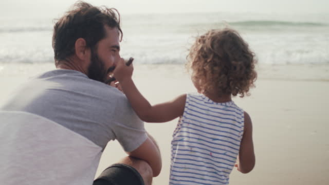 vidéos et rushes de father and son playing at water's edge on the beach - famille avec un enfant