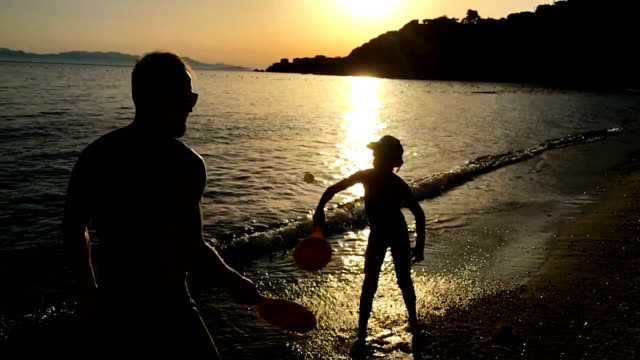 father and son playing badminton on a sunset beach - boys stock videos & royalty-free footage