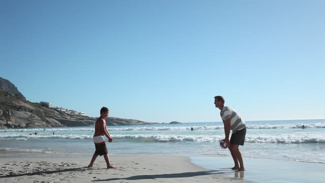 Father and son playing ball on beach