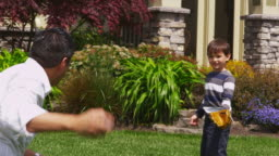 Father and son playing baseball in yard