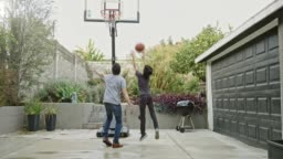 Father and son playing basketball in yard