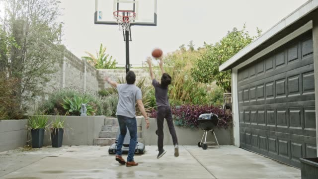 father and son playing basketball in yard - latin american and hispanic ethnicity stock videos & royalty-free footage