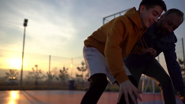 vidéos et rushes de père et fils jouant au basket-ball sur le terrain extérieur - adulte d'âge mûr