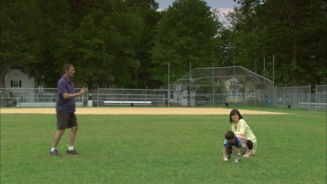 ws father and son playing catch on baseball field with mother crouching behind son/ fanwood, new jersey - つかまえる点の映像素材/bロール