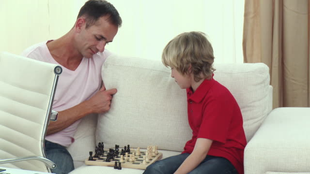ms father and son (8-9) playing chess on sofa / cape town, south africa - see other clips from this shoot 1811 stock videos & royalty-free footage