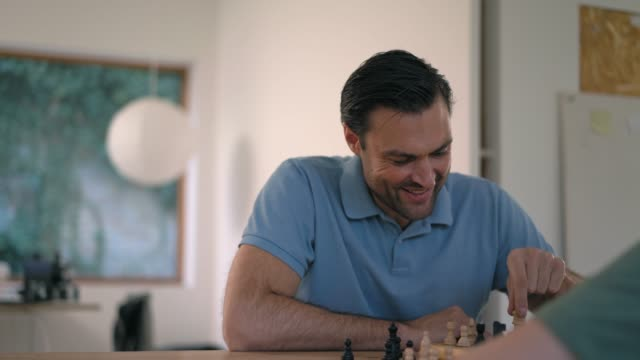 stockvideo's en b-roll-footage met father and son playing chess - spelletjesavond