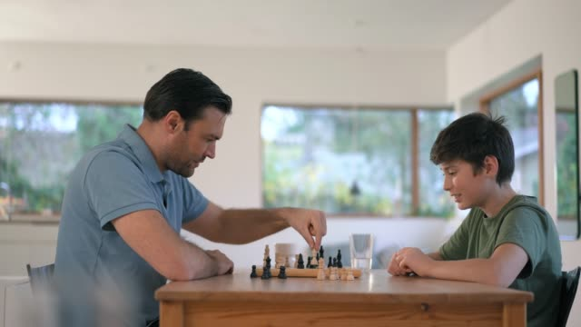 father and son playing chess - brettspiel stock-videos und b-roll-filmmaterial