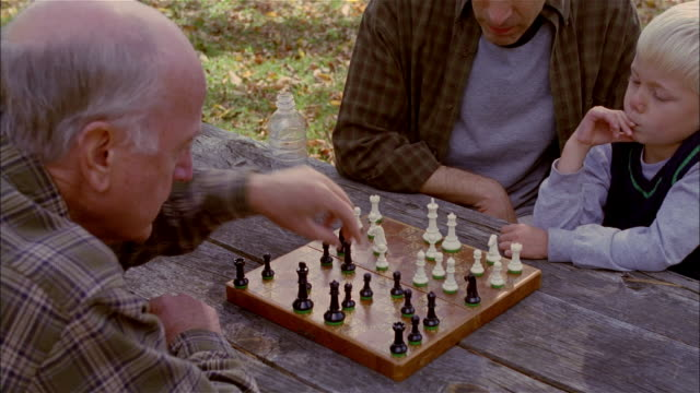 cu, ha, father and son (4-5 years) playing chess with grandfather on outdoor table, - chess stock videos & royalty-free footage