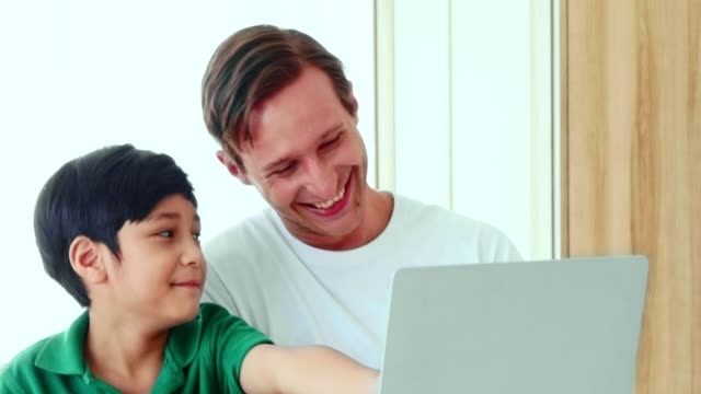vídeos y material grabado en eventos de stock de padre e hijo jugando a la computadora - intergénero