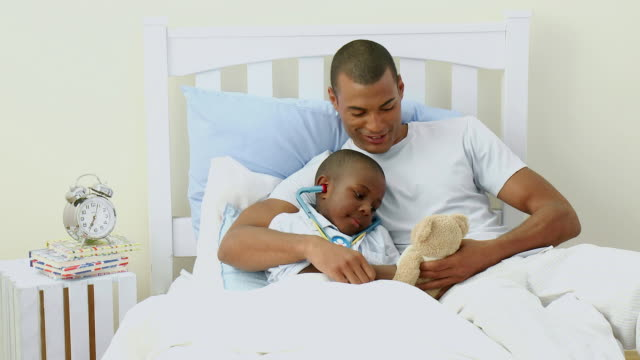 MS Father and son (4-5) playing doctors in bed / Cape Town, South Africa
