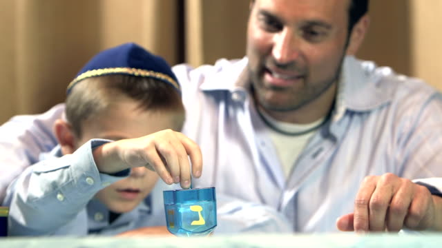 Father and son playing dreidel