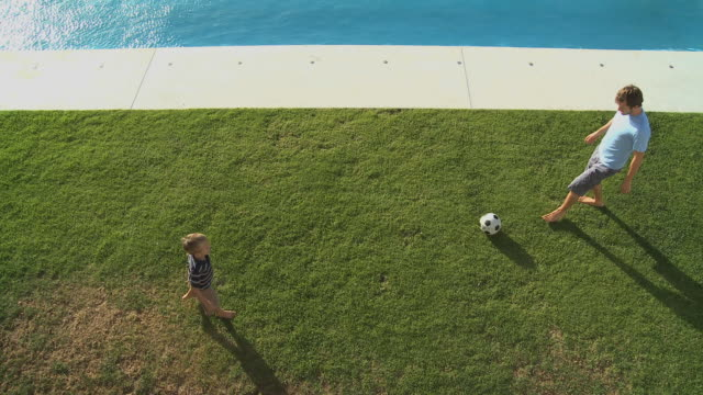 ws father and son (6-7) playing football on poolside / cape town south africa - kicking stock videos & royalty-free footage