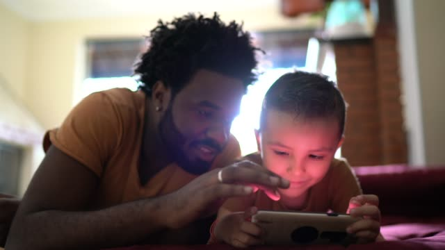 father and son playing games on smartphone - leisure games stock videos & royalty-free footage