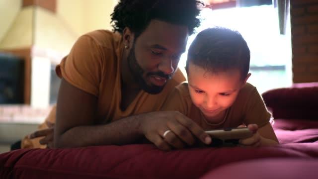 vídeos de stock, filmes e b-roll de pai e filho jogando no smartphone - filho
