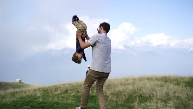 father and son playing in grassy field on mountain top - dress stock videos & royalty-free footage