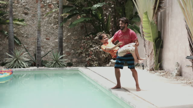 vídeos de stock, filmes e b-roll de father and son playing in pool of holiday home - mérida yucatán