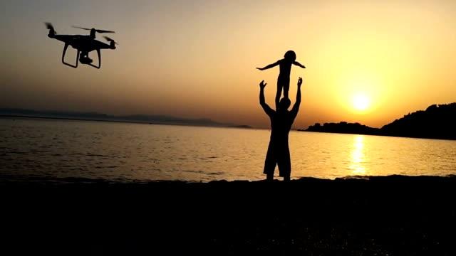 vidéos et rushes de père et fils jouant sur une plage du coucher du soleil - son