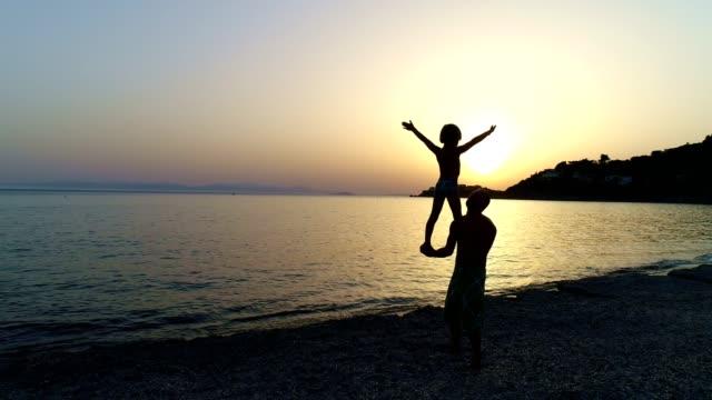 vídeos y material grabado en eventos de stock de padre e hijo jugando en una playa al atardecer - padre soltero