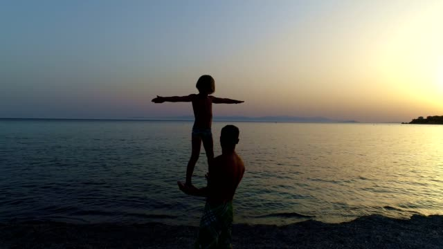 father and son playing on a sunset beach - strength stock videos & royalty-free footage