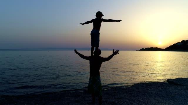vídeos de stock e filmes b-roll de father and son playing on a sunset beach - fenómeno natural