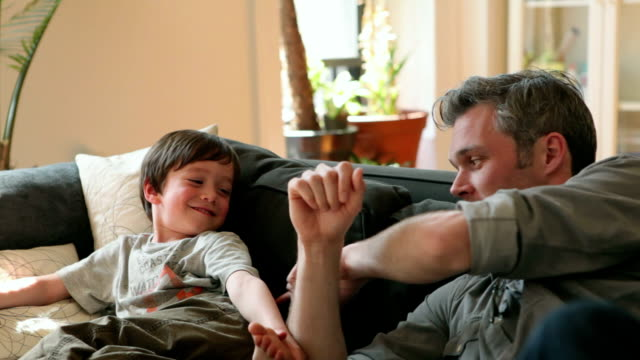 ms father and son (4-5) playing on couch in living room / brooklyn, new york city, usa - tickling stock videos & royalty-free footage