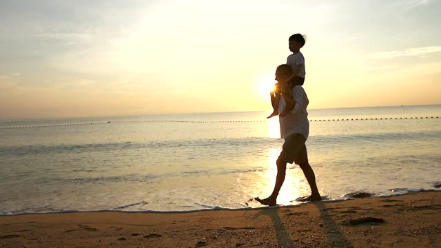 vídeos y material grabado en eventos de stock de padre e hijo jugando en la playa al amanecer, pasan tiempo de calidad en familia juntos. - articulación humana