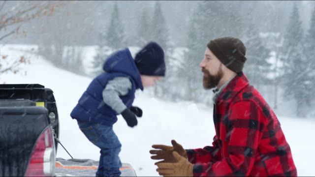 father and son playing outdoors in a winter snowstorm - woolly hat stock videos and b-roll footage