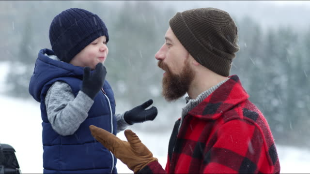 father and son playing outdoors in a winter snowstorm - genderblend video stock e b–roll