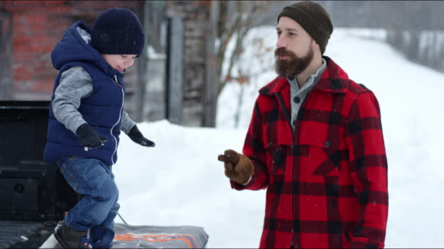 Father and son playing outdoors in a winter snowstorm