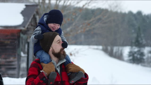 father and son playing outdoors in a winter snowstorm - genderblend stock videos & royalty-free footage