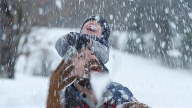 father and son playing outdoors in a winter snowstorm - 2 3 jahre stock-videos und b-roll-filmmaterial