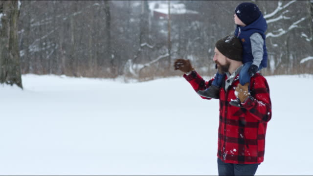 father and son playing outdoors in a winter snowstorm - ウィンターコート点の映像素材/bロール